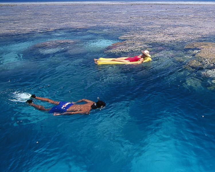 Woman floating on raft and man snorkeling along ocean reef