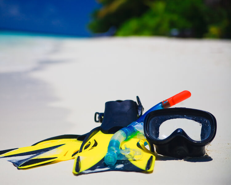 Snorkel Mask, Snorkel Fins, and Snorkel laying on a tropical beach