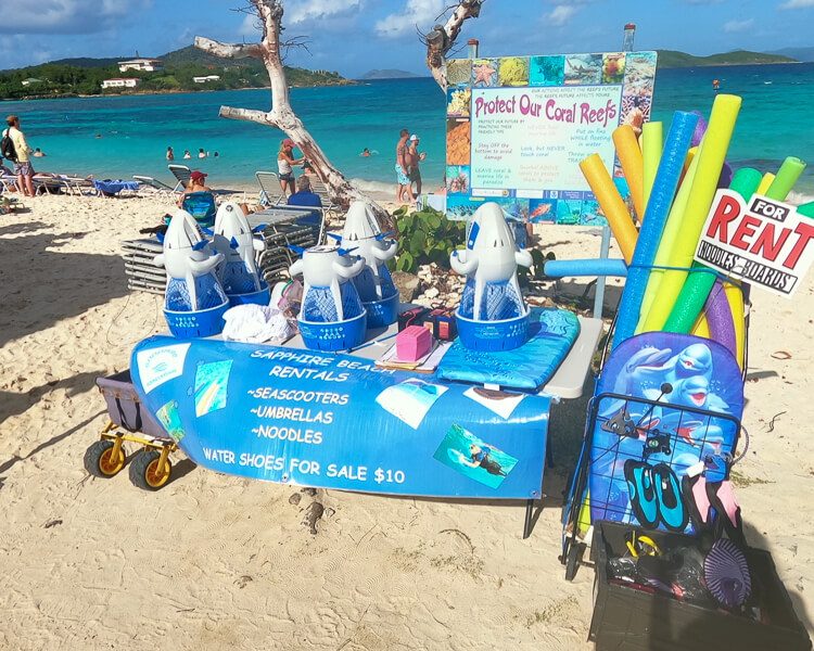 rental gear on table- snorkel bobs, beach noodles, water shoes, and sign listing all rentals