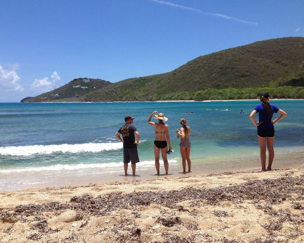 people standing on the beach at the end of the reef bay trail on St. John, USVI