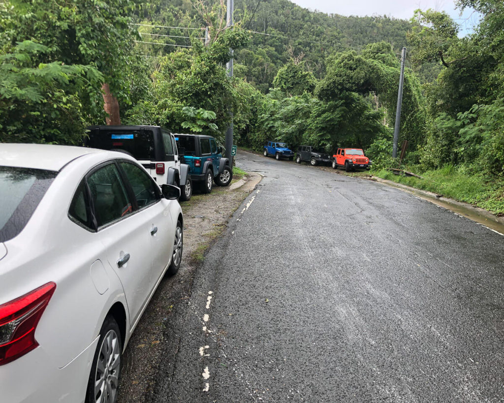 cars parked along the road at the entrance to the reef bay trail on St. John