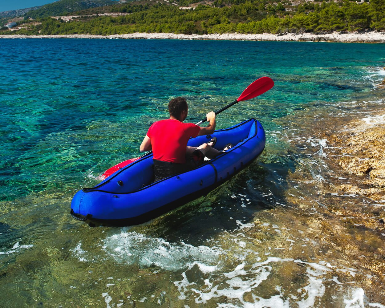 man paddling inflatable kayak along rocky coast