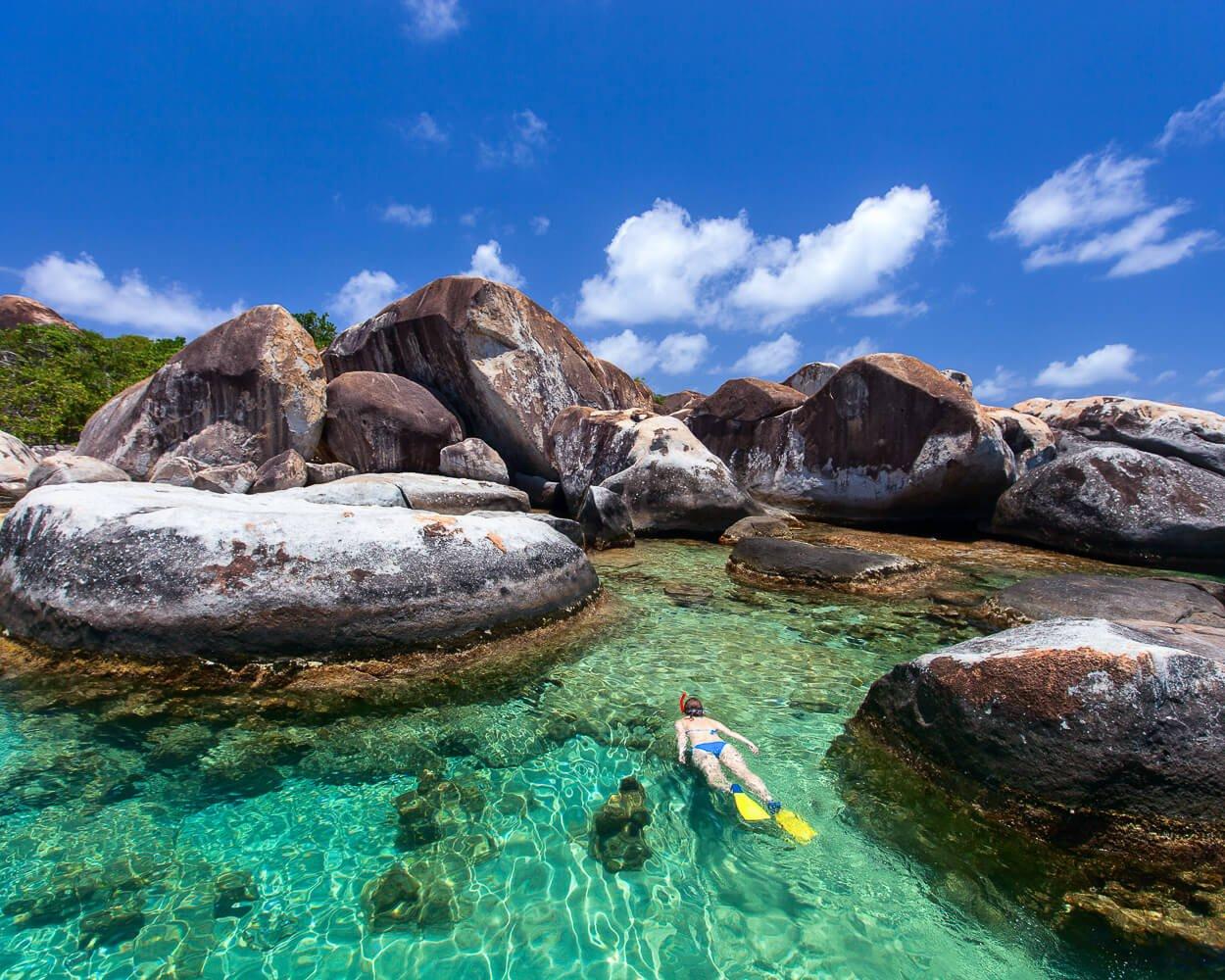 aerial view of woman snorkeling among boulders at The Baths in Virgin Gorda, British Virgin Islands