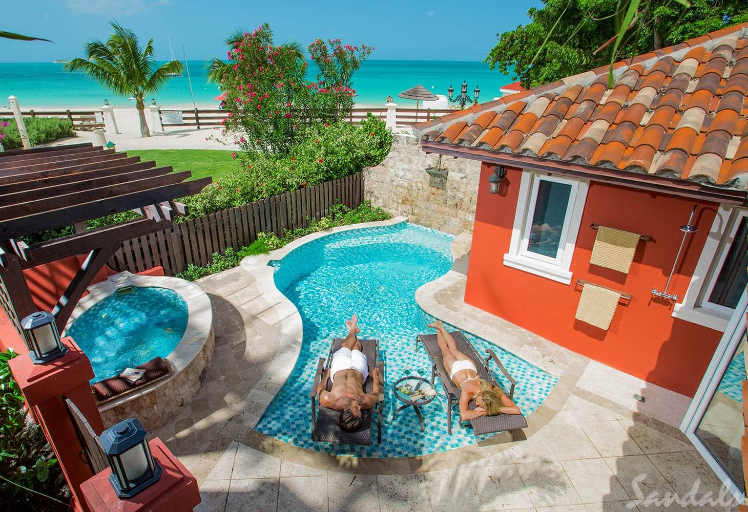 couple rest in pool at villa at Sandals Antigua