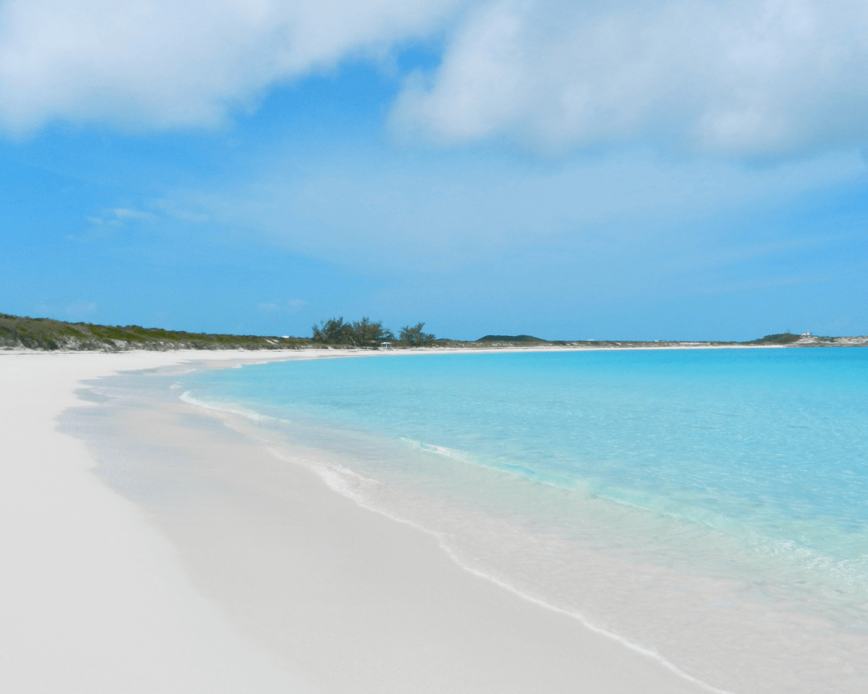 looking down the shore with on a white sand beach on Exuma in the Bahamas